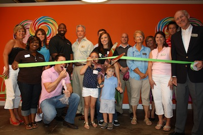 Owner Nikki Hawks Jones, assisted by her children, cuts the ribbon.