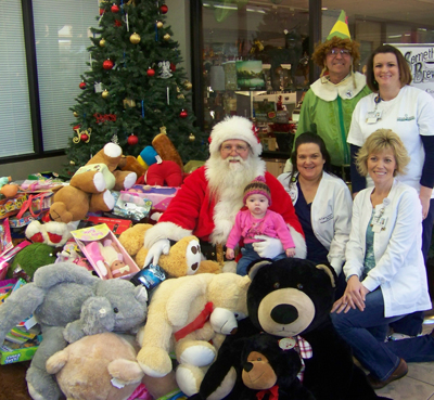 Conway Regional's Jo Lynne Gasaway, Theresa Tidwell, Jeanie Hernandez and Macee Raye Tidwell join Santa and Buddy the Elf with toys collected by area bikers for pediatric patients at the hospital.