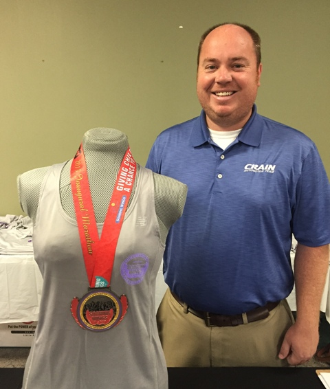 Brett Berry of Crain Automotive with the Soaring Wings Marathon medal which will be presented during the inaugural event.