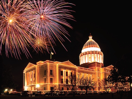 Fireworks and Christmas lights illuminate the state Capitol.